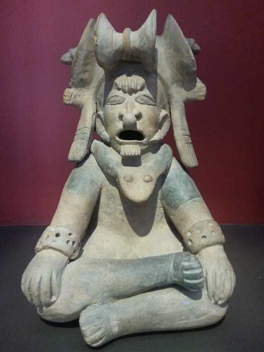 A man of high rank modelled in lotus position. His headdress with great horns and the snake-shaped necklace are typical of a shaman from the Bahia (500 BC-500 AD) culture of Ecuador. Artifact at Casa del Alabado: Museo de Arte Precolombino, Quito, Ecuador. (Credit: Alicia McDermott)